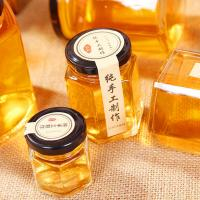 China Hexagon Clear Glass Storage Bottle 100ml 500ml With Metal Lid For Honey Cream wholesale